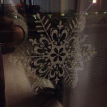 Kijk een lelijke foto van een sneeuwvloksticker op het raam